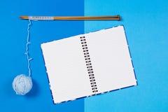 Stricknadeln, blauer Garnball und offenes Papiernotizbuch auf blauem Hintergrund Stockfotografie