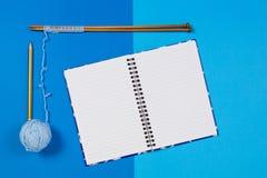 Stricknadeln, blauer Garnball und offenes Papiernotizbuch auf blauem Hintergrund Lizenzfreie Stockbilder