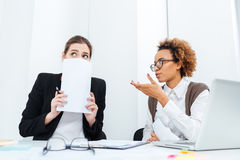 Strict african businesswoman director talking with her scared young employee. Serious strict african american businesswoman director sitting and talking with her Royalty Free Stock Images