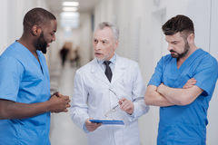 Strict aged practitioner consulting young colleagues in the hospital. Sharing precious experience. Concentrated experienced aged practitioner standing in the royalty free stock images