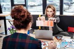 Strict blonde-haired designer showing her assistant colors stock photography