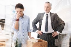 Strict boss dismissing a young sad woman. You are dismissed. Cheerless young women holding the box with her belonging and standing in the office while her boss Royalty Free Stock Image