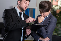 Strict boss talking with secretary. Strict boss talking with his young secretary Stock Photos