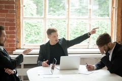 Strict boss telling upset employee to leave room during briefing stock photos