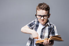 Strict boy in glasses with book in hands, Royalty Free Stock Images
