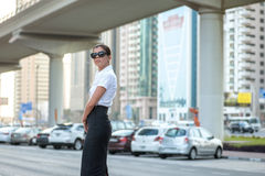 Strict business. Confident arabic businesswoman standing. In the street in formal attire. Businessman standing near skyscrapers in Dubai downtown in sunglasses Royalty Free Stock Photo