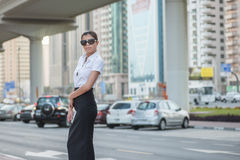 Strict business. Confident arabic businesswoman standing. In the street in formal attire. Businessman standing near skyscrapers in Dubai downtown in sunglasses Stock Photos