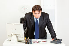 Strict businessman standing at office desk Stock Image