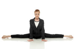 Strict businesswoman posing doing gymnastic split. Isolated on white Stock Image