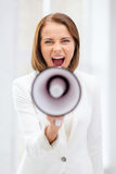 Strict businesswoman shouting in megaphone. Business and communication, bad boss concept - strict businesswoman shouting in megaphone in office Stock Photo