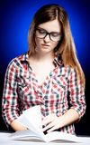 Calm young woman with nerd glasses learning diligently Royalty Free Stock Photos