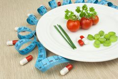 Strict diet against obesity. Dietary vegetable diet. Tomatoes on a plate. Raw vegetables on a white plate and a measuring tape. Royalty Free Stock Photography