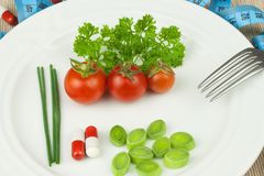 Strict diet against obesity. Dietary vegetable diet. Tomatoes on a plate. Raw vegetables on a white plate and a measuring tape. Stock Photos
