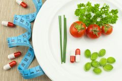Strict diet against obesity. Dietary vegetable diet. Tomatoes on a plate. Raw vegetables on a white plate and a measuring tape. Royalty Free Stock Images