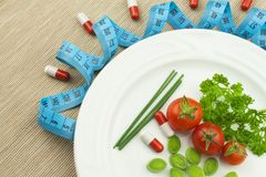 Strict diet against obesity. Dietary vegetable diet. Tomatoes on a plate. Raw vegetables on a white plate and a measuring tape. Royalty Free Stock Photo