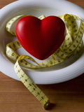 Strict diet. Plate with a heart and a tape measure on a wooden table Royalty Free Stock Image