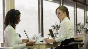 Strict female team leader checking papers with employee, brainstorming project. Stock footage Royalty Free Stock Image
