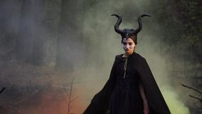 Strict girl in the image of Maleficent in a mystical and secret forest