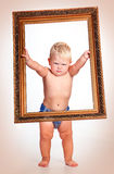 Strict a little boy holding the frame. Portrait of a cute boy without diapers in picture frame Royalty Free Stock Photography