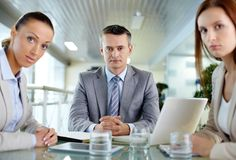 Strict look. Serious boss looking at camera with his two employees sitting near by Stock Photography