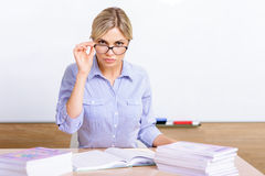 Strict-looking teacher sitting at the desk Royalty Free Stock Photography