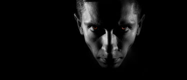 Strict male face in the dark, fiery eyes, a monochrome image, wi Stock Images
