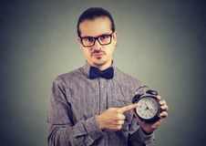 Strict man pointing at clock. Formal man in eyeglasses reminding about punctuality pointing at clock and looking at camera stock images