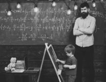 Strict math teacher checking pupil s work. Blond schoolboy solving equation at chalkboard. Preschool education concept.  royalty free stock images