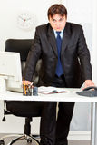 Strict modern businessman standing at office desk Stock Photos