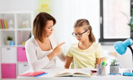 Strict mother talking to daughter doing homework stock images
