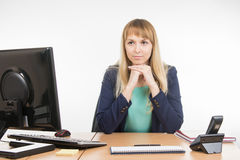 Strict office a specialist sitting at a desk and looking at visitor Royalty Free Stock Images