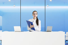 Strict receptionist with clipboard in blue office Royalty Free Stock Images