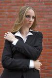 Strict schoolteacher. Standing near a red brick wall Stock Image