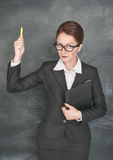 Strict teacher with chalk and folder. Strict teacher in glasses with chalk and folder royalty free stock photo