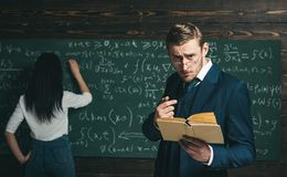 Strict teacher in glasses giving explanations while holding book. Tutor helping his young female student with math. Private education concept stock photography