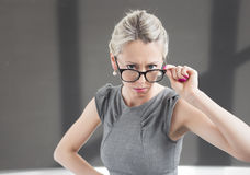 Strict teacher looking through glasses with serious expression royalty free stock photo