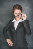 Strict teacher looking at someone. On the school blackboard background Royalty Free Stock Photos