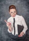 Strict teacher showing finger. Strict teacher in eyeglasses with folder showing finger stock photography