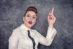 Strict teacher showing finger. Strict teacher in eyeglasses showing finger on the school blackboard background stock photography