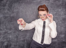 Strict teacher showing on someone by finger. Strict teacher in eyeglasses showing on someone by her finger stock photography