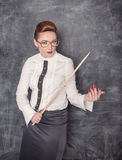 Strict teacher with wooden pointer. Looking at someone stock photography