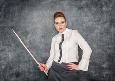 Strict teacher with wooden pointer. Looking at someone royalty free stock photography