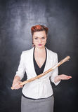 Strict teacher with wooden stick on blackboard background Stock Images