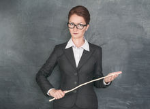 Strict teacher with wooden stick. Looking at someone royalty free stock photo
