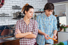 Strict unhappy woman cooking with her husband on kitchen Stock Photography