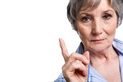 Strict woman. Photo of elderly female with her forefinger pointed upwards on white background Royalty Free Stock Images