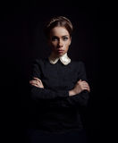 Strict woman in black clothes. Strict woman on a black background Royalty Free Stock Image