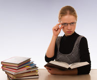 Strict woman with a book sitting at table. Strong young woman with book sitting at table stock photos