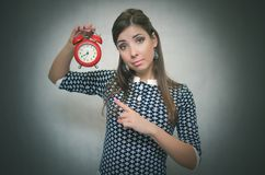 Strict woman boss with red alarm clock on gray background. Strict boss woman holding in hands red alarm clock and showing time by her index finger. Job or stock image