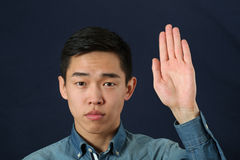 Strict young Asian man giving the stop sign stock photo